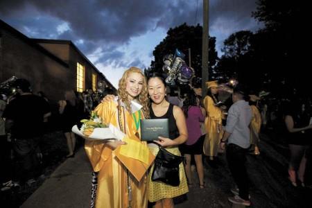 Gincia Portillo, left, and her friend Kyong Haeshin, right, show off their diplomas.