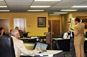 JLB Partners developers Hudson Hooks, brown suit, and Scott Schlosser, black suit, hold up a concept drawing for the Sandy Springs Gateway project during the June 20 Planning Commission Meeting. The Planning Commission, left, voted to approve zoning for the project.