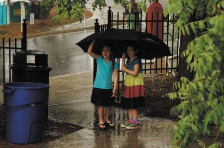 Hunter Reith Thomas, 5, at left, and Charlotte Cloud, 5, anxiously wait under a large umbrella while their parents quickly pack up everything for the ride home.