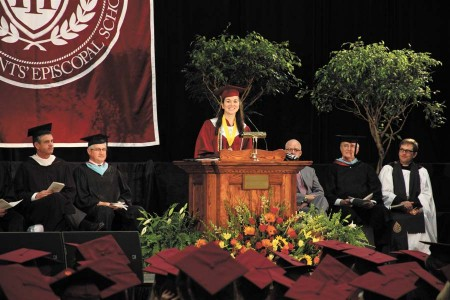 At the podium, Valedictorian Kendall Jackson delivers her address to fellow graduates as, center, Upper School Principal Chris Durst, and Associate Headmaster Rick Betts, right, look on.