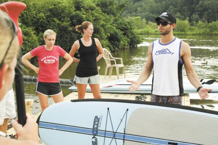Samantha Black, front left, along with Katie Devitt, center, and Kelly Berrall, right, listen to instructor John Sloan give tips on stand up paddleboarding.