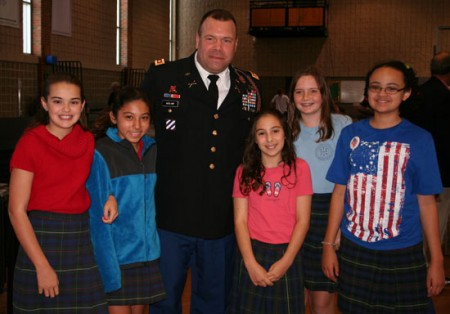 Lt. Col. Chris Auclair addressing the audience and posing with some St. Martin's students. (Special to Reporter Newspapers.)