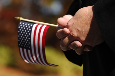 An observer holds an American flag during a Veterans Day ceremony at Brook Run Park in Dunwoody. Photo by: Phil Mosier