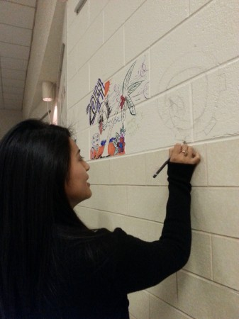 "Chamblee Charter High School senior Jessica Cruz adds to the ""Graffitit Wall"" in the cafeteria of the soon-to-be demolished, old Chamblee High building."