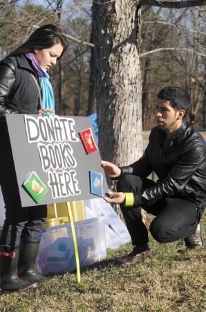 Dalia Alvarez, left, helps Edgar Remerez put up a donation sign.