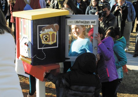 """Arwen Coy, 9, takes a peek into the """"little free library"""" unveiled at Briarwood Park on Jan. 16. The Cross Keys Foundation, a public charity that supports education in the Brookhaven area, was instrumental in opening the free library, which features a post-mounted, book swap unit."""