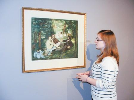 "Oglethorpe freshman Jordan Michels looks at Manet's 19th century oil on canvas, ""Le Dejeuner sur J'Herbe"" (Luncheon on the Grass)."