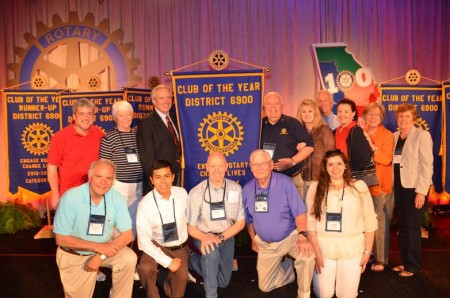District Governor Blake McBurney (standing left of the banner) and Jim Squire (standing right of the banner), along with a number of club members who attended the conference.