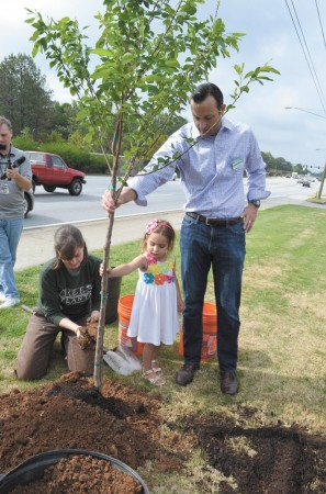 J.D. Clockdale and his daughter, Ella, 3, steady a tree while Susan Pierce Cummingham of Trees Atlanta shovels soil around it.