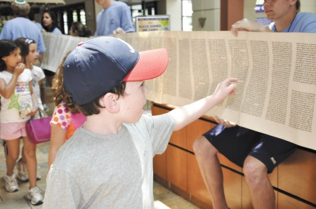The Torah is unveiled to children during a Shavuot observance at the Marcus JCC in Dunwoody in a previous year.