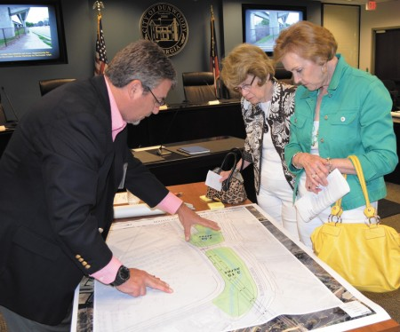 Consultant Ray Strychalski, left, points out features of a 5-acre park planned for under the Dunwoody MARTA station rails to Jan Slater, back left, and Charlene Thurman, during a public meeting April 22 at Dunwoody City Hall.