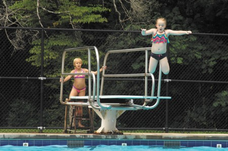 Kyndra Leaphart, 7, does take a leap into the Murphey Candler pool, while her cousin Kiara McCoy, 9, awaits her turn during a day out on June 6. The city of Brookhaven took control over managing the Lynwood, Briarwood and Murphey Candler pools from DeKalb County this year.