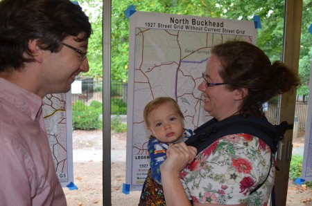 Eloise Foltz and her 13-month-old son Oliver and husband Michael reviewed maps at the July 15 meeting of the North Buckhead Civic Association at St. James UMC. The association is developing a master plan for its community.