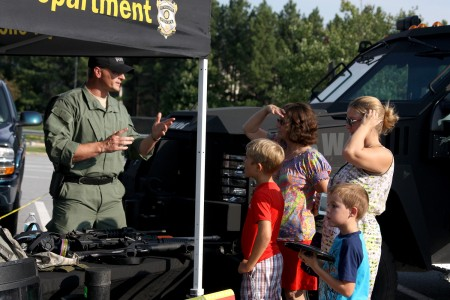 Officer Lee Hasseltine at the 2014 National Night Out in Dunwoody discusses the SWAT team purpose and shows the gear used to the Smith family of Dunwoody. Clockwise from back: Sharon Wright, Nicole Smith, Gage Smith, 6, and Dillon Smith, 8. (File photo)