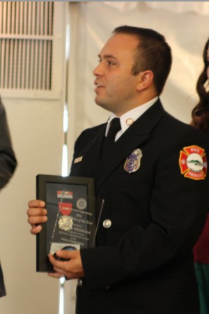 Firefighter Matthew Hildebrand accepts the Firefighter of the Year Award during The Rotary Club luncheon Sept. 22.