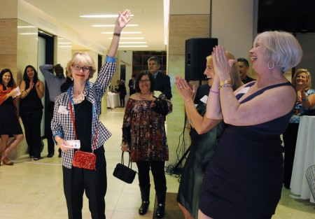From right, Susan Mitchell, Jany Brown, and councilwoman Lynn Deutsch applaud as Su Ellis' (left) name is drawn during a raffle for a Big Green Egg during Monarchs & Margaritas on March 29, 2014.