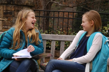 Middle schoolers Nora Rosenfeld, 11, left, and Lucy Grey Sheilds, 12, share a joke and a sunny afternoon in the 'Triangle Park,' which was landscaped by the Castlewood Civic Association. The park is a place parents meet their kids after school.