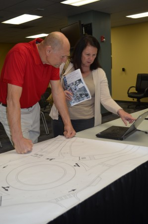 John and Donna Bendik check drawings and a computer animation showing how the proposed roundabouts would handle traffic.