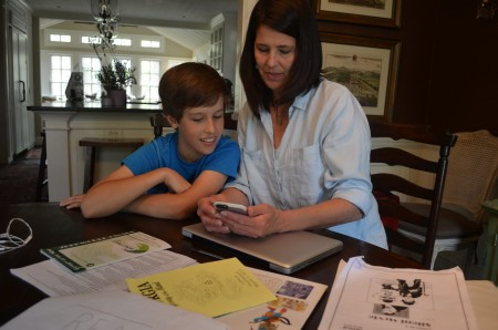 Jackson Langley and his mom, Leslie, look over photos from their  Odyssey of the Mind competitions.