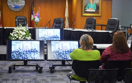 Molly Boyenga, left, and Melissa Rixley watch the funeral of former Sandy Springs Mayor Eva Galamos as its streamed to screens in Sandy Springs City Hall on April 21.