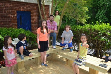 Justin McCurdy, center, joined a group of High Point Elementary tudents on the new deck he and his dad built for the school. Left to right, the students are Khana Cooper, 5, Samuel Cooper, 8, Ivey Boyd, 11, McCurdy, Eden Boyd, 9 (in tree), Tatum Boyd, 6, and Zahria Whittington, 8.