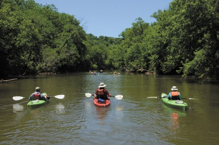 Novice or beginning paddlers are able to navigate the shoals in the Etowah River's Class I water. Here Ellen and Brian Cardin kayak with Joe Kidd (center).