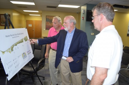 Gene Jordan, left (pink shirt), Christopher Kingsbury of Moreland Altobelli Associates Inc., center (blue jacket), and John Stewart, right (white shirt), discuss plans for the proposed trail and stream improvements planned as part of the passive park planned on the south side of Abnernathy Road. They met durng a public presentation of the plans on June 30 at Sandy Springs City Hall. Photo by Joe Earle.