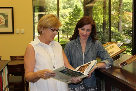 Kinsey Harper, left, president of the board of Cherokee Garden Library, and library director Staci Catron page through a book from the collection. Photo by Mary Helen Kelly