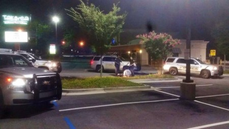 """Photo posted on Dunwoody Police Department Facebook page of officers interacting with a """"man in crisis"""" who was taken to a local hospital instead of jail after jumping a patio fence at a restaurant."""