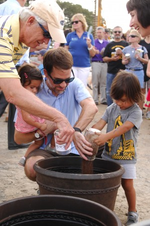 Whispering Pines residents (from left) Mel Mobley and father Vann McNeill with children Ravi, 2, and Seema, 1, contribute local soil to the City Springs site on Sept. 20. (Photo by Phil Mosier)