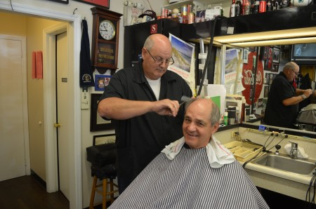 """Walter """"Tommy"""" Thomas gives Charlie Schreeder a trim in his barbershop, a business the Thomas family has been operating in the same spot in Buckhead for 56 years."""