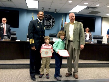 DeKalb County Fire Chief Darnell Fullum recognizes Ethan and Brian Wittenton at the Sept. 28 Dunwoody City Council meeting. Mayor Mike Davis on the right. In the background from left to right: Council members Jim Riticher and Lynn Deutsch.