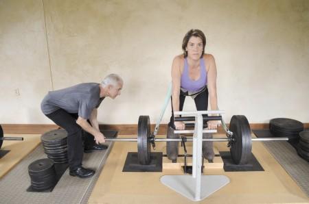"""Vladimir Chubinsky keeps a watchful eye on client Beth Nowak as she lifts weights during a """"gravitational wellness"""" program."""