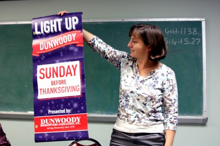 Stacey Harris, a Dunwoody Homeowners Association board member, shows off thenew Light Up Dunwoody banners during the Oct. 4 meeting.