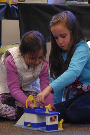 sisters Madeline Martin (left), 6, and Claire Martin, 9, play at a table where used toys were being sold. (Photo by Phil Mosier)