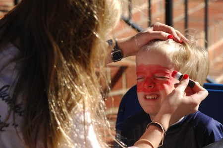 Connor Park, 4, gets his face painted by St. Martin's graduate Gracie Stovall. (Photo by Phil Mosier)