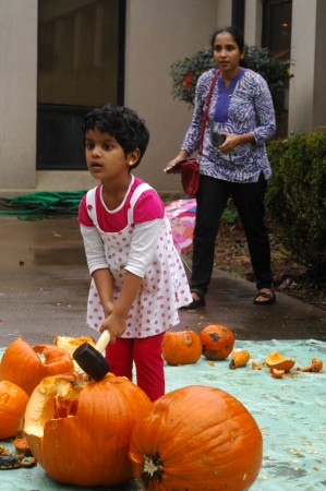 Shireya Sumesh, 4, dents a pumpkin while her mother, Rashmi Sumesh looks on. (Photo by Phil Mosier)