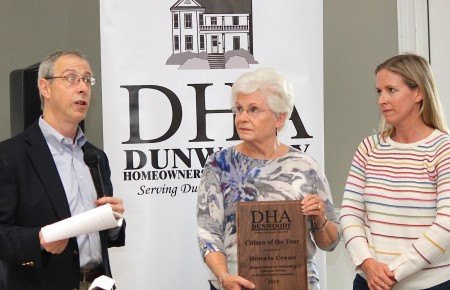 Dunwoody HOA President Robert Wittenstein presents Marie Crean and her daughter a plaque honoring Dennis Crean as Citizen of the Year. (Photo Dyana Bagby)