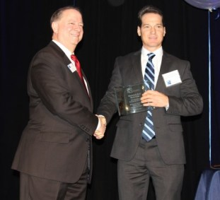 Christopher Groom (right) of Mountain High Outfitters accepts the Business of the Year award from new Buckhead Business Association president David Coxon at the BBA's annual luncheon Feb. 25 at Flourish. (Photo John Ruch)