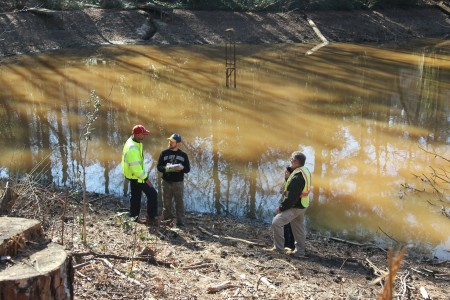 From left, Philip Walker of the city of Sandy Springs; state Safe Dams Program inspectors Bobby Sauer Jr. and Skylar Barger; and Knut Hauer of the city of Atlanta's Department of Watershed Management inspect Powers Lake dam in Sandy Springs. (Photo John Ruch)