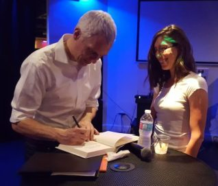 Ryan Gravel signs a book for Cross Keys High School teacher Rebekah Morris at Brookhaven's Royal Lounge. (Photo John Ruch)