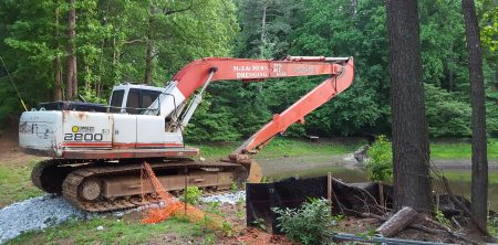An earthmover rests atop the Lake Forrest Dam on Lake Forrest Drive May 11. (Photo John Ruch)