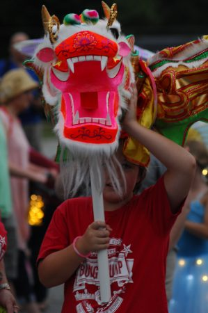 North Springs United Methodist Church; Saturday June 18, 2016 8:00pm. Sandy Springs Hospitality and Tourism hosted the Inaugural Sandy Springs Lantern Parade. Participants paraded down Morgan Falls Road to Morgan Falls Overlook Park. Paraders gather and organized in church parking lot before parade began. Chinese Dragon the Stevens family, Mom Tamra Stevens, Dad Matt Stevens, and children Luke Stevens (10yr) [short hair], and James Stevens (13yr) [long hair].