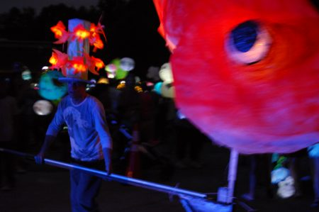 """North Springs United Methodist Church; Saturday June 18, 2016 8:00pm. Sandy Springs Hospitality and Tourism hosted the Inaugural Sandy Springs Lantern Parade. Participants paraded down Morgan Falls Road to Morgan Falls Overlook Park. Leading the parade, Dave Lind rolling the giant gold fish we had made. """"I have over fifty hours in the making in this fish."""" Said Lind."""