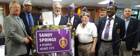 "Sandy Spring City Council members John Paulson (far left) and Tibby DeJulio (center, holding proclamation), celebrate the ""Purple Heart Medal City"" designation with local veterans at the June 7 City Council meeting. (Photo John Ruch)"