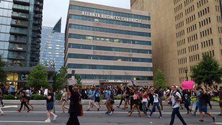 """Protesters chant """"Hands up, don't shoot!"""" while marching on Peachtree Road. (Photo John Ruch)"""