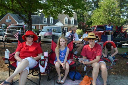Karen Dhaenens, left, and Katelyn and Pam Austin await the start of the parade.