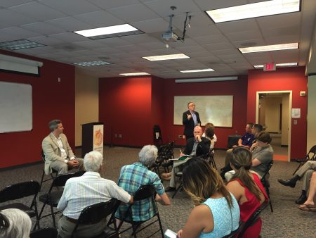 Brookhaven City Manager speaks at the July 28 town hall while Mayor John Ernst (seated, right) looks on. (Photo Grace Huseth)