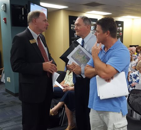 Sandy Springs City Councilmember Chris Burnett (left), who called for the Sandy Springs Circle meeting, speaks with residents before the presentation. (Photo John Ruch)