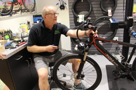 Eric Hunger works on an e-bike at his ElectroBike store in Brookhaven. (Photo Dyana Bagby)